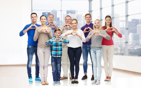 Photo pour gesture, family, generation and people concept - group of smiling men, women and boy showing heart shape hand sign over empty office room or home - image libre de droit