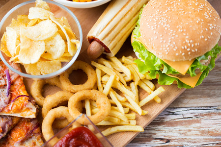 Photo pour fast food and unhealthy eating concept - close up of hamburger or cheeseburger, deep-fried squid rings, french fries hotdog and potato chips on wooden table top view - image libre de droit
