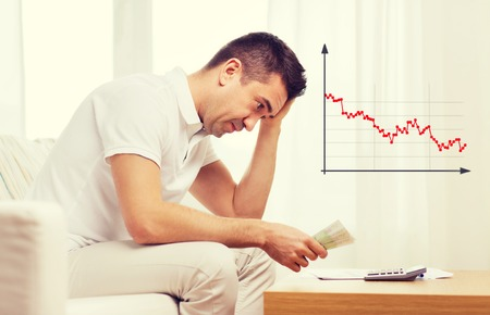 business, savings, financial crisis and people concept - upset man with money and calculator at home