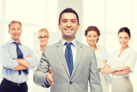 Photo pour business, people, gesture, partnership and greeting concept - happy smiling businessman in suit with team over office room background shaking hand - image libre de droit