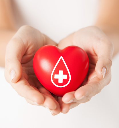 Foto de healthcare, medicine and blood donation concept - female hands holding red heart with donor sign - Imagen libre de derechos