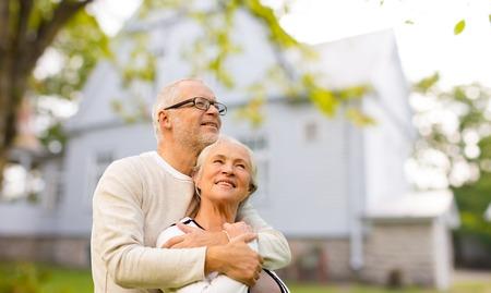 Foto de family, age, home, real estate and people concept - happy senior couple hugging over living house background - Imagen libre de derechos