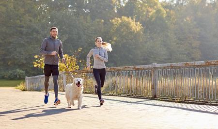 Foto de fitness, sport, people and lifestyle concept - happy couple with dog running outdoors - Imagen libre de derechos