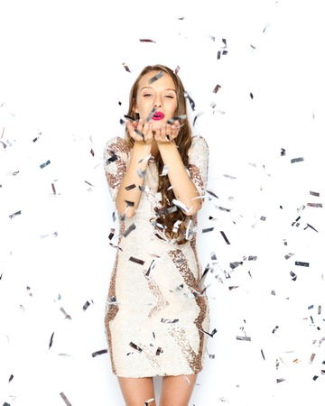 Photo for people, holidays, gesture and glamour concept - happy young woman or teen girl in fancy dress with sequins and confetti at party sending blow kiss - Royalty Free Image