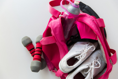 Photo pour sport, fitness, healthy lifestyle and objects concept - close up of female sports stuff in backpack and dumbbells - image libre de droit