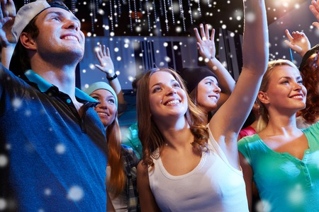 Foto de party, holidays, celebration, nightlife and people concept - smiling friends waving hands at concert in club and snow effect - Imagen libre de derechos