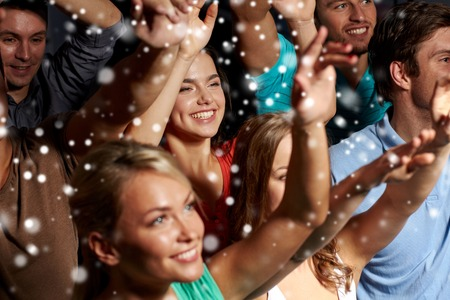 Photo for party, holidays, celebration, nightlife and people concept - smiling friends waving hands at concert in club and snow effect - Royalty Free Image