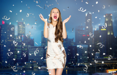 Photo for people, holidays, emotion and glamour concept - happy young woman or teen girl in fancy dress with sequins and confetti at party over night singapore city background - Royalty Free Image