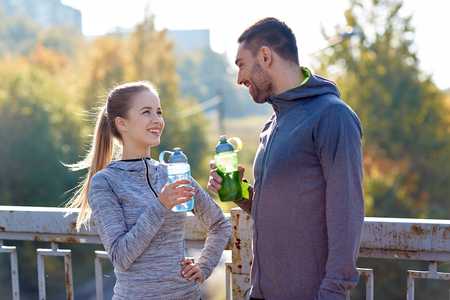 Photo pour fitness, sport, people and lifestyle concept - smiling couple with bottles of water outdoors - image libre de droit