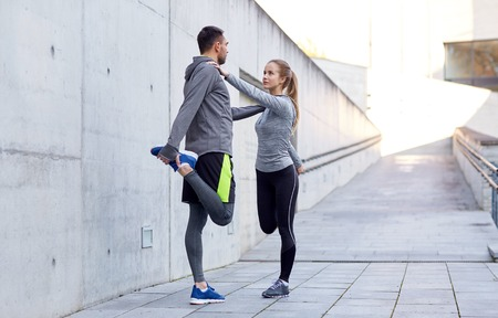 fitness, sport, people and lifestyle concept - smiling couple stretching leg outdoors