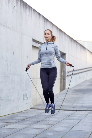 Foto de fitness, sport, people, exercising and lifestyle concept - woman skipping with jump rope outdoors - Imagen libre de derechos