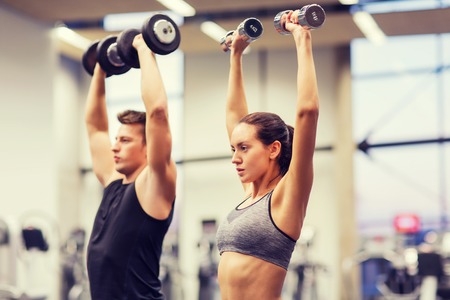 Photo pour sport, fitness, lifestyle and people concept - smiling man and woman with dumbbells flexing muscles in gym - image libre de droit