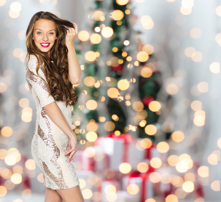 Foto de people, holidays, hairstyle and fashion concept - happy young woman or teen girl in fancy dress with sequins touching long wavy hair over christmas tree lights background - Imagen libre de derechos