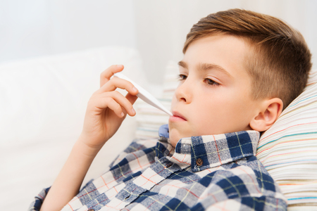 childhood, healthcare and medicine concept - ill boy with flu measuring temperature by thermometer at home