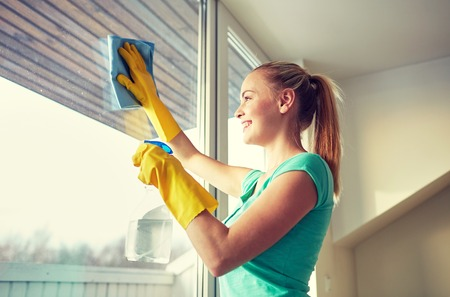 Photo for people, housework and housekeeping concept - happy woman in gloves cleaning window with rag and cleanser spray at home - Royalty Free Image