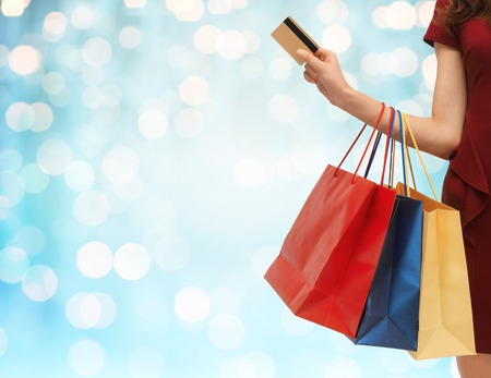 people, sale and consumerism concept - close up of woman with shopping bags and bank or credit card over blue holidays lights background