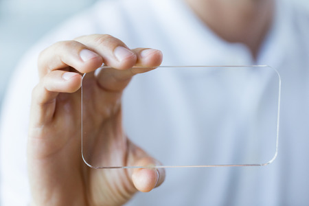 Photo for business, technology and people concept - close up of male hand holding and showing transparent smartphone at office - Royalty Free Image