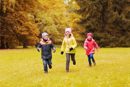 Foto de autumn, childhood, leisure and people concept - group of happy little kids playing tag game and running in park outdoors - Imagen libre de derechos