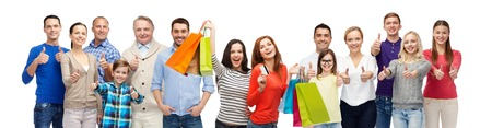 gesture, sale and people concept - group of smiling men, women and kids showing thumbs up and holding shopping bags with credit card