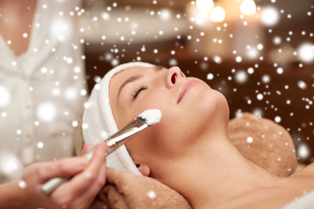 Photo pour people, beauty, spa, cosmetology and skincare concept - close up of beautiful young woman lying with closed eyes and beautician hand applying facial mask by brush in spa salon with snow effect - image libre de droit