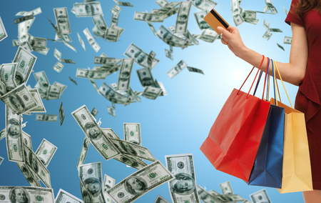 Photo for people, sale, finance and consumerism concept - close up of woman with shopping bags and bank or credit card over blue background and money rain - Royalty Free Image