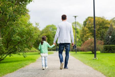 Foto de family, parenthood, fatherhood, adoption and people concept - happy father and little girl walking in summer park - Imagen libre de derechos