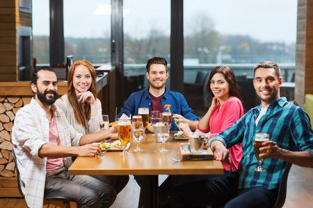 Photo pour leisure, eating, food and drinks, people and holidays concept - smiling friends having dinner and drinking beer at restaurant or pub - image libre de droit