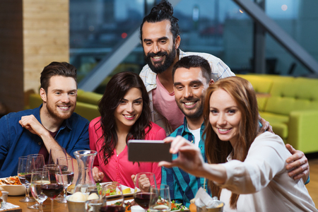 Photo pour leisure,technology, friendship, people and holidays concept - happy friends having dinner and taking selfie by smartphone at restaurant - image libre de droit