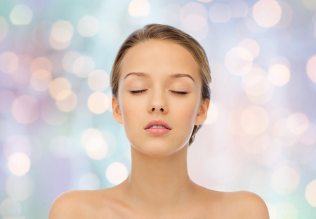 Photo pour beauty, people and health concept - young woman face with closed eyes and shoulders over blue holidays lights background - image libre de droit