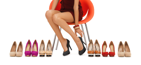 Photo pour people, fashion, shopping, footwear and style - close up of woman sitting on chair and trying on high heeled shoes - image libre de droit