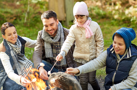 Photo pour camping, travel, tourism, hike and people concept - happy family roasting marshmallow over campfire - image libre de droit