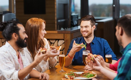 Photo for leisure, food and drinks, people and holidays concept - smiling friends eating pizza and drinking beer at restaurant or pub - Royalty Free Image