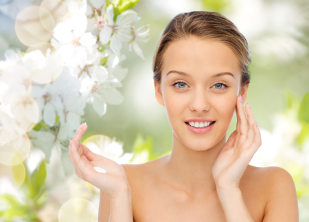Photo for beauty, people, cosmetics, skincare and health concept - happy smiling young woman applying cream to her face over green natural background with cherry blossoms - Royalty Free Image