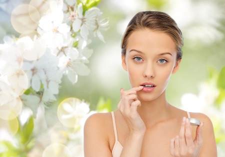 Photo pour beauty, people and lip care concept - young woman applying lip balm to her lips over green natural background with cherry blossoms - image libre de droit