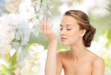 Foto de beauty, aroma, people and body care concept - young woman smelling perfume from wrist of her hand over green natural background with cherry blossoms - Imagen libre de derechos