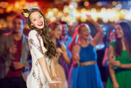 Photo for people, holidays, nightlife and celebration concept - happy young woman or teen girl in party dress and princess crown at night club party over crowd and lights background - Royalty Free Image