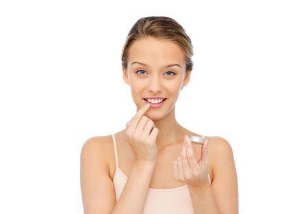 Photo pour smiling young woman applying lip balm to her lips - image libre de droit
