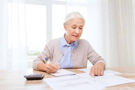 Photo for senior woman with papers or bills and calculator writing at home - Royalty Free Image