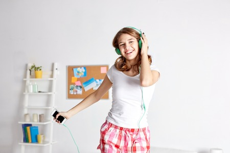 Photo pour happy woman or teenage girl in headphones listening to music from smartphone and dancing on bed at home - image libre de droit