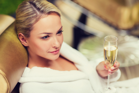 beautiful young woman in white bath robe lying on chaise-longue and drinking champagne at spa