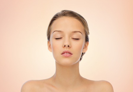 Photo pour young woman face with closed eyes and shoulders over beige background - image libre de droit