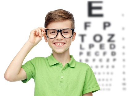 Foto de happy smiling boy in green polo t-shirt in eyeglasses over eye chart background - Imagen libre de derechos
