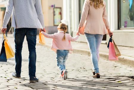 Foto de close up of happy family with little child and shopping bags in city - Imagen libre de derechos