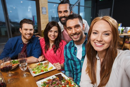 Photo for happy friends having dinner and taking selfie by smartphone at restaurant - Royalty Free Image