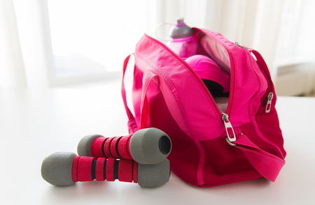 close up of female sports stuff in bag and dumbbells