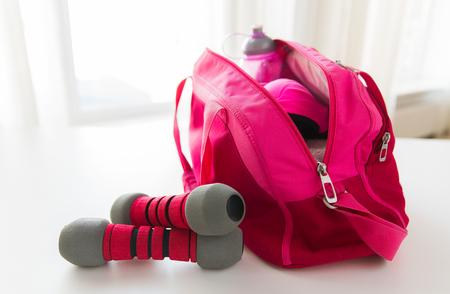 Photo pour close up of female sports stuff in bag and dumbbells - image libre de droit