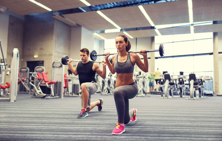 Foto de young man and woman with barbell flexing muscles and making shoulder press lunge in gym - Imagen libre de derechos