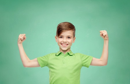 Foto de happy smiling boy in green polo t-shirt showing strong fists over green school chalk board background - Imagen libre de derechos