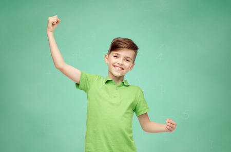 Photo for happy smiling boy in green polo t-shirt showing strong fists over green school chalk board background - Royalty Free Image