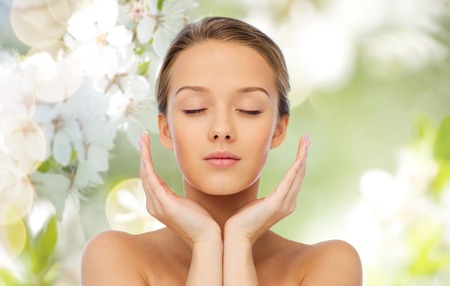 Foto de beauty, people, skincare and health concept - young woman face and hands over cherry blossom background - Imagen libre de derechos
